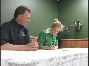 Kaila Martin signs her letter of intent alongside Viterbo coach Jim Socha