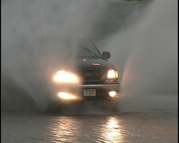 Truck drives through standing water on Stewart Avenue