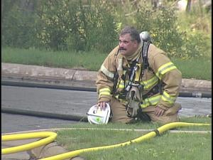 Firefighter struggles with the steamy weather while fighting the blaze