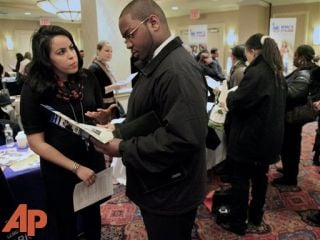In this Jan. 25, 2012 photo, Daniela Silvero,left, an admissions officer at ASA College, discuss job opportunities with Patrick Rosarie, who is seeking a job in IT, during JobEXPO's job fair, in New York. (AP Photo/Bebeto Matthews)