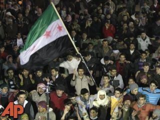 In this Sunday, Feb. 5, 2012 photo, Syrian protesters wave a revolutionary flag during a demonstration in Idlib, Syria. (AP Photo)