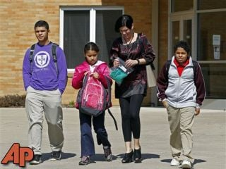 In this March 16, 2011 file photo, Heather Coffy, right center, leaves the St. Monica School with her children, left to right, Delano Coffy, 15, Alanna Marshall, 8, and Darius Coffy, 11, in Indianapolis. (AP Photo/Michael Conroy, File)