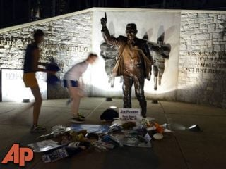 People visit the Joe Paterno statue early Sunday July 22, 2012. in State College, Pa. (AP Photo/John Beale)