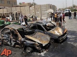 People inspect the aftermath of a car bomb attack in Baghdad's Shiite enclave of Sadr City, Iraq, July 23, 2012. (AP Photo/Karim Kadim)