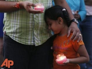 A man holds his child during a candle light vigil for the victims of the Sikh Temple of Wisconsin shooting in Milwaukee Sunday, Aug 5, 2012. (AP Photo/Jeffrey Phelps)