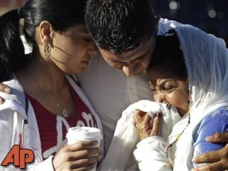 Amardeep Kaleka, son of the president of the Sikh Temple of Wisconsin, center, comforts members of the temple, Monday, Aug. 6, 2012, in Oak Creek, Wis., where a gunman killed six people a day earlier. (AP Photo/M. Spencer Green)