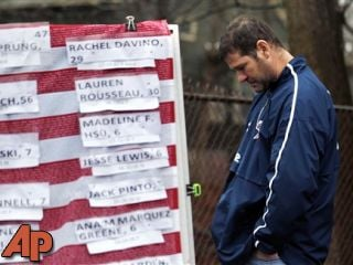 A man pays respects near a U.S. flag donning the names of victims on a makeshift memorial in the Sandy Hook village of Newtown, Conn., as the town mourns victims killed in a school shooting, Monday, Dec. 17, 2012. (AP Photo/Julio Cortez)