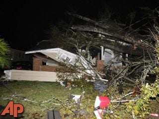 A house in the Midtown section of Mobile, Ala. is damaged after a tornado touched down Tuesday, Dec. 25, 2012. (AP Photo/AL.com, Mike Kittrell)