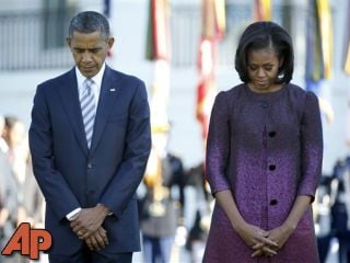 President Barack Obama and first lady Michelle Obama pause during a moment of silence to mark the 11th anniversary of the Sept. 11th attacks, Tuesday, Sept. 11, 2012, at the White House. (AP Photo/Carolyn Kaster)