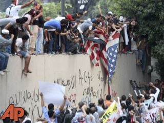 Protesters destroy an American flag pulled down from the U.S. embassy in Cairo, Egypt, Tuesday, Sept. 11, 2012. (AP Photo/Mohammed Abu Zaid)