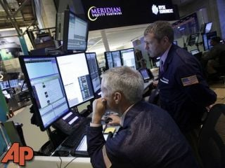 In this Thursday, Sept. 13, 2012 photo, a pair of traders work in their booth on the floor of the New York Stock Exchange, in New York. (AP Photo/Richard Drew)