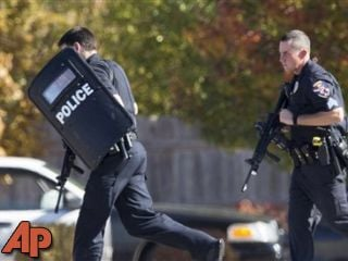 Police and swat team members respond to a call of a shooting at the Azana Spa in Brookfield, Wis. Sunday, Oct. 21, 2012. (AP Photo/Tom Lynn)