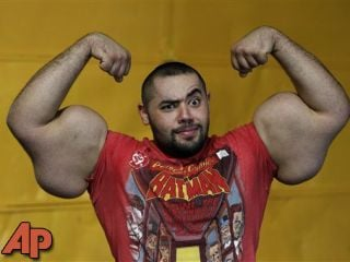 In this photo taken, Friday, Nov. 16, 2012, Egyptian Body builder Moustafa Ismail poses during his daily workout at World Gym in Milford, Mass. (AP Photo/Stephan Savoia)