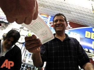 Keith Ganatra and his wife Anita Ganatra, owners of the Del Monte Market, help customers waiting to buy Powerball lottery tickets, Nov. 28, 2012, in Phoenix.(AP Photo/Ross D. Franklin)