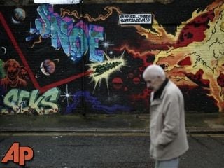 A man walks past street art in east London, Dec. 20, 2012. (AP Photo/Matt Dunham)