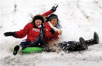 (AP Photo/Enid News and Eagle, Bonnie Vculek). Kamika Ralstin,left, Sarah Blakley, back, and Claudia Huerta sled down the slope of the South Van Buren overpass Thursday, Feb. 21, 2013, in Enid, Okla.