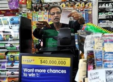 (Bergen County NJ), Tyson Trish). Baiju Amin hands lottery tickets to a customer at Union Food Store in Totowa, N.J. on Sunday, March 24, 2013.