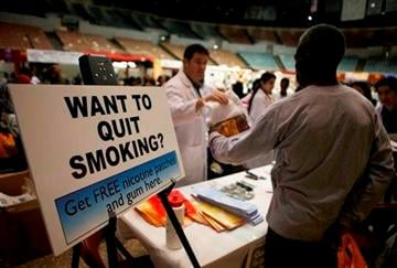 (AP Photo/Damian Dovarganes, File). FILE- In this Tuesday, April 27, 2010, file photo, smokers without medical insurance receive free nicotine patches and gum at the Remote Area Medical (RAM) clinic inside the Los Angeles Sports Arena in Los Angeles.