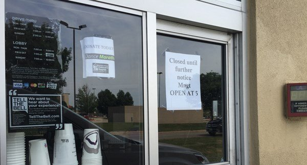 "Sign on the Taco Bell's drive-thru window says ""Closed until further notice ... Open at 5"" on the morning of Tuesday, Aug. 4, 2015. (Lauren Moss, KWWL)"